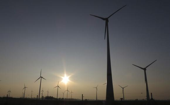 The sun sets behind power-generating wind turbines from a wind farm near the village of Ludwigsburg